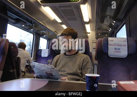 Il passeggero leggendo un giornale in una prima classe carrello di un treno in Inghilterra