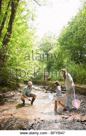 La famiglia gioca nel flusso di paese Foto Stock