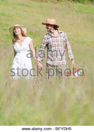 Matura in cappelli a piedi attraverso Prato Foto Stock