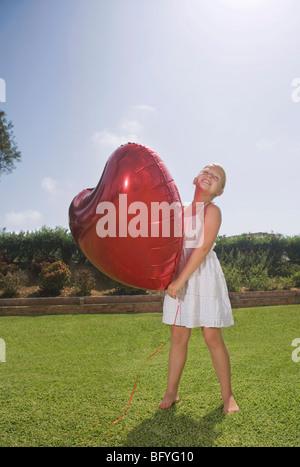 Ragazza giovane azienda grande cuore rosso palloncino Foto Stock