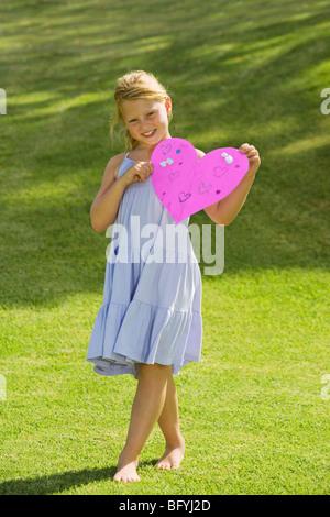 Ragazza giovane azienda rosa cuore di carta