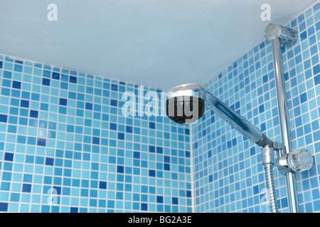 Testa di doccia nel bagno di blu di piastrelle a mosaico