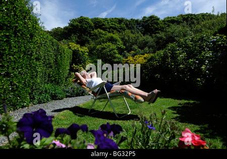 La vecchiaia LADY PENSIONATO GODE DI PENSIONE di prendere il sole nel giardino Inglese UK Foto Stock