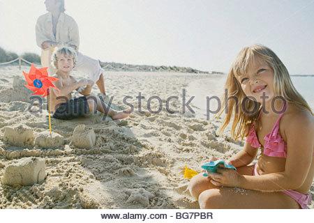 Famiglia giocando in sabbia sulla spiaggia Foto Stock