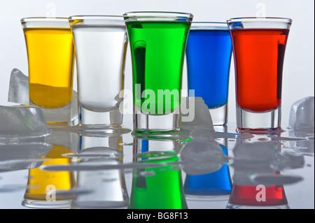 Still-life da cinque piccole pile dal vetro, riempito cocktail di colore con la riflessione e il ghiaccio Foto Stock