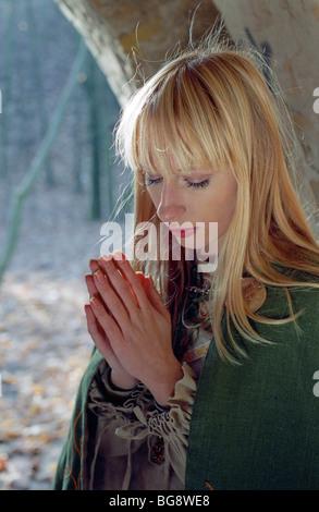 Donna medievale pregando in castello Foto Stock