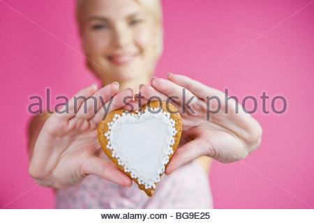 Una giovane donna tenendo fuori un cuore di biscotto a forma di Foto Stock