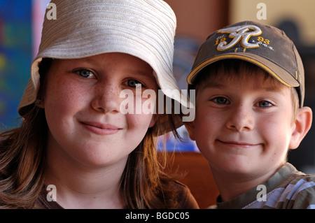 Ritratto di una giovane ragazza con le lentiggini e un cappello e un giovane ragazzo che indossa un berretto Foto Stock