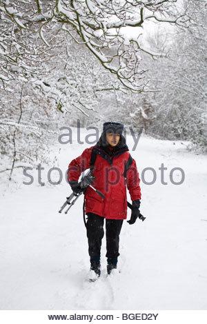 Fotografo femmina porta un treppiede attraverso un paesaggi innevati in inverno Foto Stock