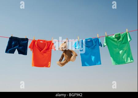 Abbigliamento per bambini e orso di peluche su una linea di lavaggio contro un cielo blu. India Foto Stock