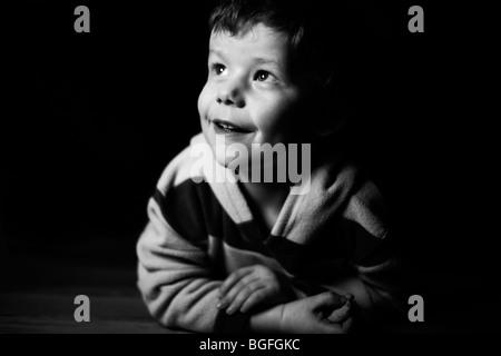 Foto in bianco e nero di un 5 anno vecchio ragazzo in illuminazione drammatica
