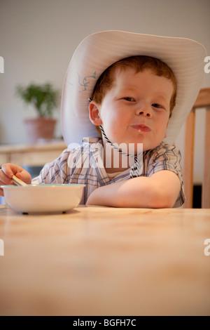 Un bambino di cinque anni, ragazzo di mangiare il suo cereale a colazione.
