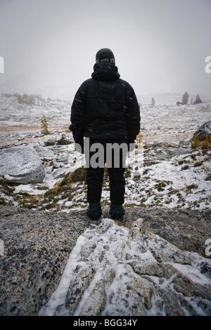 Una persona tutta vestita di nero abiti invernali guardando fuori su un paesaggio alpino in una tempesta di neve, Foto Stock