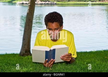 Giovane 16-17 anno vecchio ragazzo adolescente giovane uomo si rilassa rilassante lettura nel parco sotto agli alberi Foto Stock