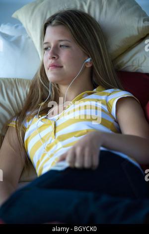 Giovane donna sdraiata su letto, ascolto di MP3 player Foto Stock