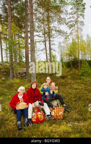 Famiglia con cestini di funghi nella foresta Foto Stock