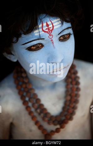 Ragazzo indiano, faccia dipinta come il dio indù Shiva contro uno sfondo nero. India