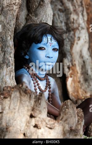 Ragazzo indiano, faccia dipinta come il dio indù Shiva seduto in un vecchio ceppo di albero. Andhra Pradesh, India