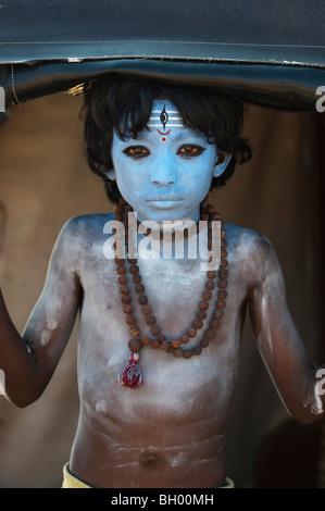 Ragazzo indiano, faccia dipinta come il dio indù Shiva in piedi in un rickshaw. Andhra Pradesh, India