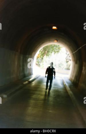 Sfocata misteriosa figura maschile camminare nel tunnel. Foto Stock