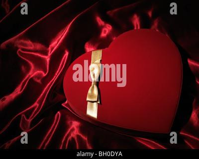 Cuore rosso a forma di scatola regalo con un golden bow