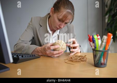 Una imprenditrice facendo una fascia di gomma a sfera con un ufficio con un espressione di concentrazione Foto Stock