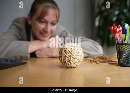 Una imprenditrice guardando un fatto a mano la banda di gomma sfera su una scrivania in ufficio, sorridente Foto Stock