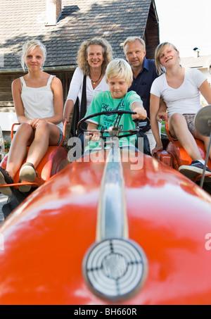 Famiglia seduto sul trattore Foto Stock