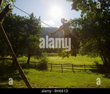 Ragazza su altalena in agriturismo Foto Stock