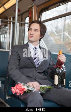 Imprenditore nel tubo, champagne, fiori Foto Stock