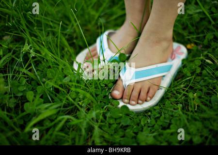 6 anno vecchia ragazza con flip flop di erba Foto Stock