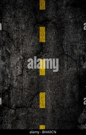 Asfalto texture di sfondo con una divisa linea gialla Foto Stock