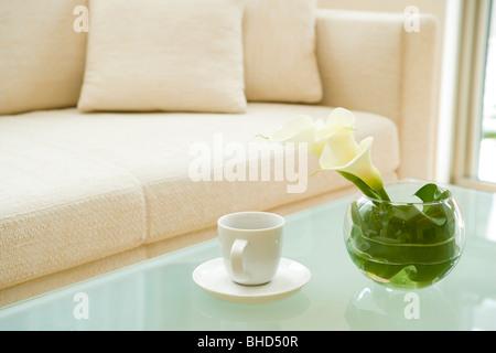 Tavolino con fiori in vaso e tazza da caffè Foto Stock