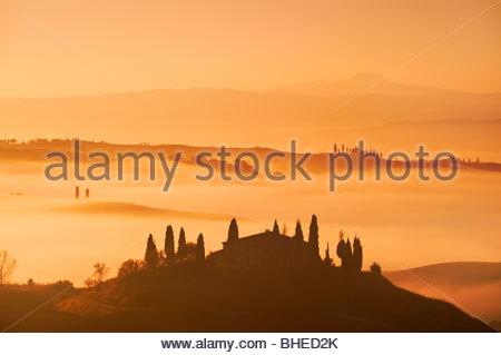 Early Morning mist circonda il casale a Belvedere, nei pressi di San Quirico d'Orcia, Val d'Orcia, Toscana, Italia. Foto Stock