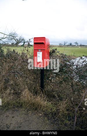 Rosso casella postale sul pilastro solo nella campagna del Suffolk Bawdsey Inghilterra Foto Stock