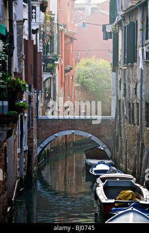Piccolo ponte su uno stretto, tranquillo canale di Venezia, Veneto, Italia Foto Stock