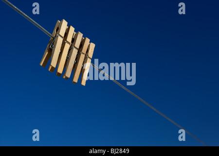 Cinque clothespegs close up appeso su una linea di lavaggio con cielo blu Foto Stock