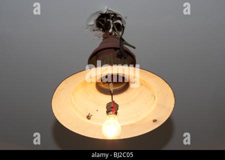 Vecchio pericoloso dodgy cablaggio luce a soffitto con bulbo nudo Foto Stock