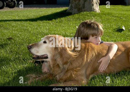 Il ragazzo si appoggia sul cane Foto Stock