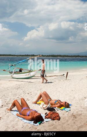 Indonesia, Lombok, Gili Trawangan, spiaggia due lucertole da mare sdraiati sulla sabbia vicino outrigger boat Foto Stock