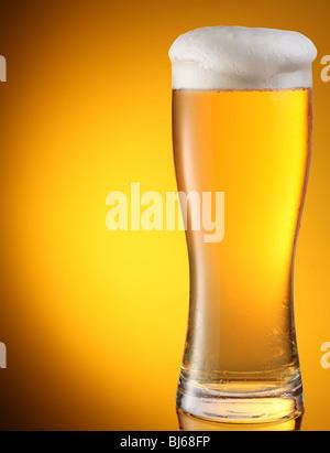 Bicchiere di birra su sfondo giallo Foto Stock