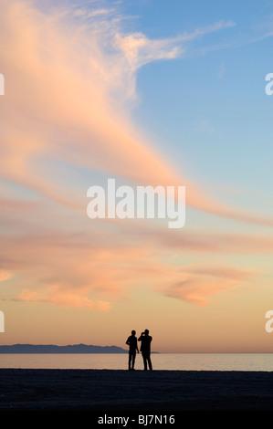 Fotografare la gente sulla spiaggia al tramonto Foto Stock