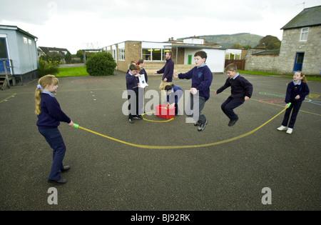Saltando, parco giochi tradizionali gioco che viene giocato sul schoolyard di una scuola primaria in Wales UK Foto Stock