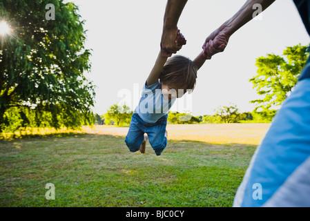 La filatura genitore little boy in posizione di parcheggio Foto Stock