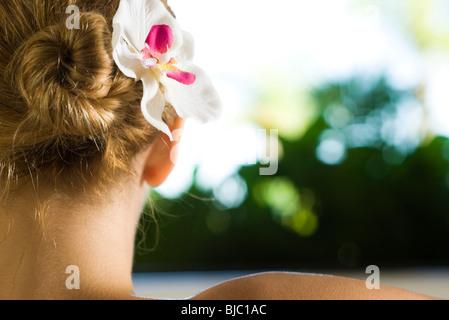Donna con orchid nei suoi capelli, close-up Foto Stock