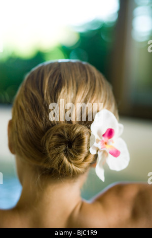 Donna con orchid nei capelli, vista posteriore Foto Stock