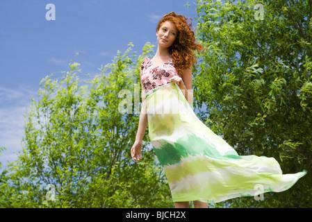 Giovane donna in piedi all'aperto, tenendo sciarpa in vento Foto Stock