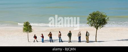 Gruppo di persone in piedi in fila chiacchierando tra due alberi sulla spiaggia Foto Stock