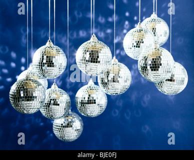 Mirroring di sfere da discoteca con macchie di luce su sfondo blu scuro Foto Stock