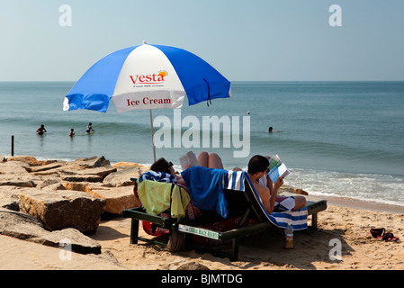 India Kerala, Vypeen Isola, Cherai Beach visitatori rilassante sotto ombrellone Foto Stock